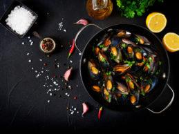 mejillones-cocinados-salsa-vino-hierbas-sarten-sobre-fondo-negro_2829-1667